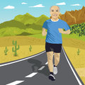 Senior man running or sprinting on road in mountains. Fit mature male fitness runner during outdoor workout Royalty Free Stock Photo