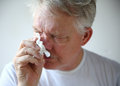 Senior man with runny nose a the flu or a cold wipes his Stock Photos