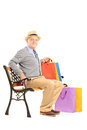 Senior man seated on a bench holding shopping bags wooden isolated white background Stock Photo