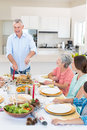 Senior man serving meal to family men at dining table Stock Photography