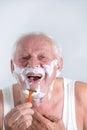 Senior man shaving his beard in bathroom Royalty Free Stock Images
