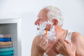 Senior man shaving his beard in bathroom Stock Images