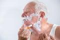 Senior man shaving his beard in bathroom Royalty Free Stock Photos