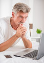 Senior man shopping online with laptop and credit card in bed Stock Photo