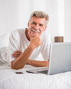 Senior man shopping online with laptop and credit card in bed Stock Photography