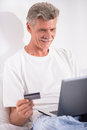 Senior man shopping online with laptop and credit card is sitting in bed Royalty Free Stock Images