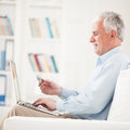 Senior man shopping online smiling men sitting in his living room and using his laptop Stock Photos