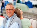 Senior man sitting back to back with his wife Royalty Free Stock Images