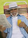 Senior Man sitting on Lawn Chair holding Newspaper and Orange Juice elevated view portrait. Royalty Free Stock Photo