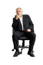 Senior man sitting on office chair thoughtful and looking at camera Royalty Free Stock Images