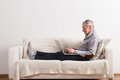 Senior man sitting on sofa, working on laptop. Royalty Free Stock Photo