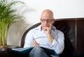 A senior man sitting taking notes in sofa Royalty Free Stock Image