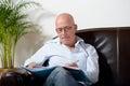 A senior man sitting taking notes in sofa Stock Photos