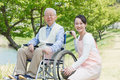 Senior man sitting on a wheelchair with caregiver Royalty Free Stock Photo