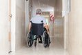 Senior man sitting in a wheelchair rear view of at hospital corridor Royalty Free Stock Photos