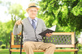 Senior man sitting on a wooden bench and reading a book in park Stock Image