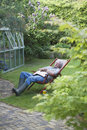 Senior man sleeping on deckchair in backyard full length of men Royalty Free Stock Photography