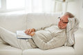 Senior man sleeping on sofa with book at home Royalty Free Stock Photo