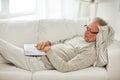 Senior man sleeping on sofa with book at home Royalty Free Stock Photo