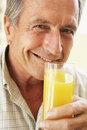Senior Man Smiling Drinking Orange Juice Stock Image
