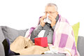 Senior man on a sofa blowing his nose in a handkerchief covered with blanket isolated white background Royalty Free Stock Photography