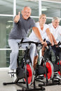 Senior man on spinning bike holding Royalty Free Stock Images