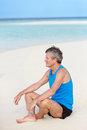 Senior man sports clothing relaxing beautiful beach happy Stock Photography