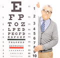 Senior man standing behind eyesight test isolated on white background shot with a tilt and shift lens Royalty Free Stock Photos