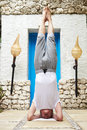 Senior man standing on head in yoga position outside of spar Royalty Free Stock Photos