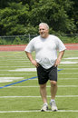 Senior man stretching exercising sports field Royalty Free Stock Photo