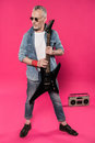 Senior man in sunglasses and denim jacket holding electric guitar and looking away Royalty Free Stock Photo