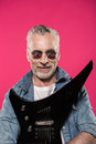 Senior man in sunglasses and denim jacket holding electric guitar and smiling at camera Royalty Free Stock Photo