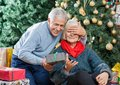 Senior man surprising woman with christmas gifts men covering s eyes while her in store Royalty Free Stock Images
