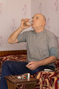 Senior man swallowing down his medication as he sits at a small table with an assortment of tablets and pills Royalty Free Stock Photos