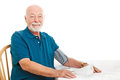 Senior man taking his blood pressure home kitchen table white background Royalty Free Stock Photo