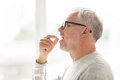 Senior man taking medicine pill at home Royalty Free Stock Photo