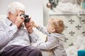 Senior man taking photo of his toddler grandson men while sitting near christmas tree at home Royalty Free Stock Image