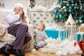 Senior man taking photo of his toddler grandson men while sitting near christmas tree at home Royalty Free Stock Photo