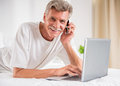 Senior man is talking by phone while lying on bed with laptop Royalty Free Stock Image