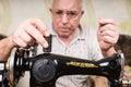 Senior Man Threading Old Fashioned Sewing Machine Royalty Free Stock Photo