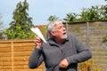 A senior man throwing a paper aeroplane or elderly having fun about to throw airplane Stock Photo
