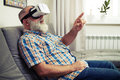 Senior man touch something with his finger using VR glasses Royalty Free Stock Photo