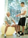 Senior man and trainer in a fitness club personal explains to men how to do exercise on ball Stock Photo