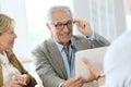 Senior man trying on eyeglasses in optical store Royalty Free Stock Photo