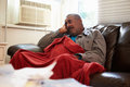 Senior man trying to keep warm under blanket at home red looking worried Royalty Free Stock Image