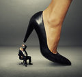 Senior man under big female heel concept photo of Royalty Free Stock Images