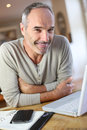 Senior man updatind schedule at home mature working from Stock Images