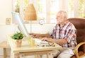 Senior man using computer at home desktop looking screen smiling Stock Images