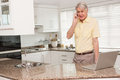 Senior man using his laptop on the phone at home in kitchen Royalty Free Stock Photos