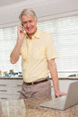 Senior man using his laptop on the phone at home in kitchen Stock Image